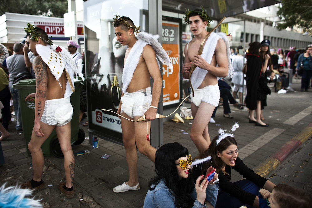 People in costumes arrive to take part in a street party for the Jewish holiday of Purim in Tel Aviv February 22, 2013. Purim is a celebration of the Jews' salvation from genocide in ancient Persia, as recounted in the Book of Esther. REUTERS/Nir Elias (ISRAEL - Tags: SOCIETY)